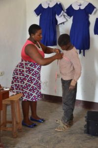 The seamstress takes the measurements for a new school uniform, as such uniforms are required in schools in Cameroon.